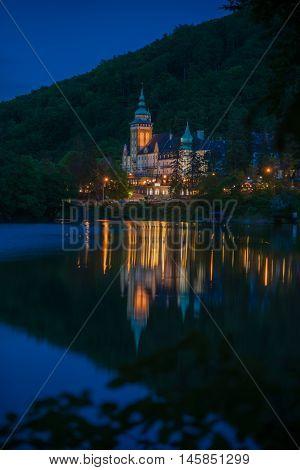 Illuminated Northern front of Lillafured palace (Miskolc Hungary) and night. Lake Hamori with reflection in foreground.
