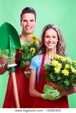 Gardening. Young couple with flowers. Over green background