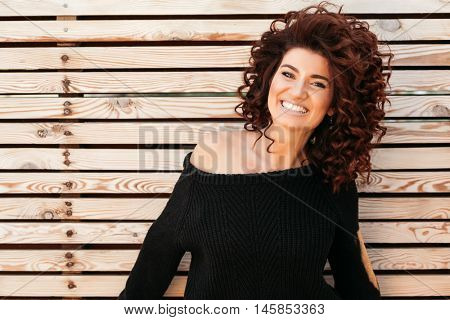 Beautiful friendly girl with curly hair wearing black sweater posing against wooden wall and smiling