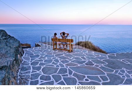 SIFNOS CASTLE CYCLADES GREECE, AUGUST 26 2016: tourists sitting on bench at Sifnos castle Cyclades Greece viewing the Aegean sea. Editorial use.