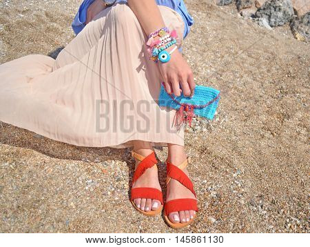 woman advertises handmade accessories on beach - greek sandals bag and jewelry