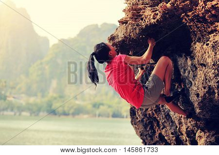 young woman rock climber climbing at seaside mountain rock poster