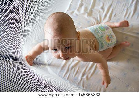 Baby in a diaper in playpen .