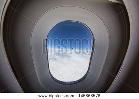 Airplane Window With Wing And Cloudy Sky Behind.