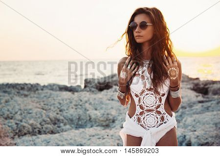 Beautiful boho styled girl wearing white crochet swimsuit with flash tattoo at the beach in sunlight