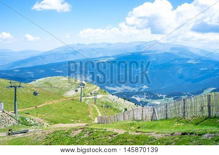 Spectacular top panoramic view of the Pyrenees mountain ridge and beautiful clouds and cable car from the peak of Tosa d´Alp, Pyrenees, Girona, Alp, Catalonia, Spain