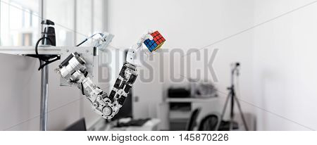 mechanized robot hand holds the objects drawn Rubik's Cube