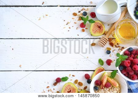 Good morning - granola with honey berries and fruits. White wooden food background top view