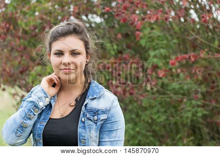 Portrait of fine teenage girl outdoors. Girl is looking at the camera.