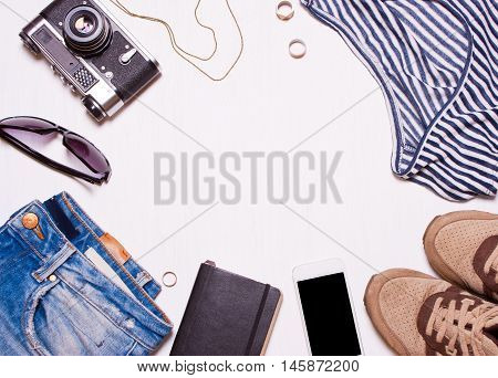 Collage of women's men's accessories clothing.Jeans T-shirt sunglasses vintage camera phone sneakers on a white background. Hipster concept creative fashionable man women
