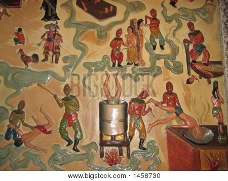 Sculpted And Painted Wall In A Buddhist Temple Showing Torture, Manado, Sulawesi Island, Indonesia