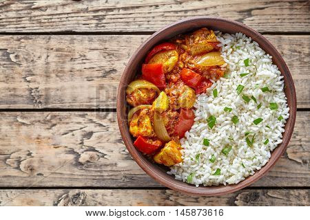 Chicken jalfrezi Indian spicy curry chilli meat with basmati rice and vegetables healthy dietetic asian food in clay dish on vintage table background.