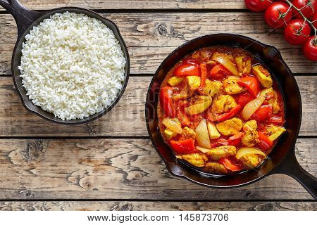 Chicken jalfrezi dietetic traditional Indian curry spicy fried meat with vegetables and basmati rice food in cast iron pan on vintage table background