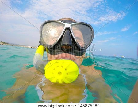 Portrait of a young woman floating and wearing snorkeling gear in the clean blue sea of Protaras Cyprus. Close up view of tube mask bikini of free diver overthe surface of the water.