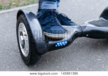 Leg men in blue sneakers and jeans standing on the blue gyroscooter platform, which is on the street. Start to using the electrical scooter, hoverboard, gyroboard or gyroscooter
