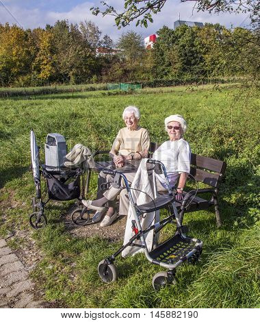 Two Elderly Ladies Enjoy The Sun At A Bench And Got There With A Rollato