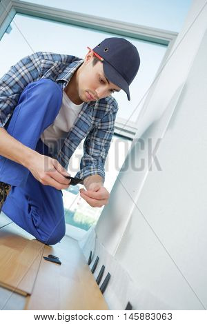 young worker in uniform installing new baseboard at home