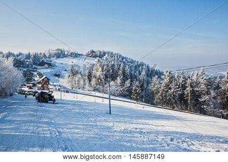 SKI CENTER KOHUTKA, CZECH REPUBLIC - JANUARY 16, 2010: Ski resort in the Czech Tatra. Frosty sunny winter day. Rolled-country skiing and ski lift passes through gentle mountain
