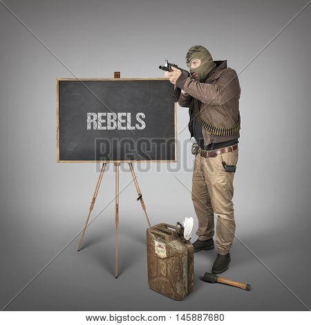 Rebels text on blackboard with terrorist holding machine gun