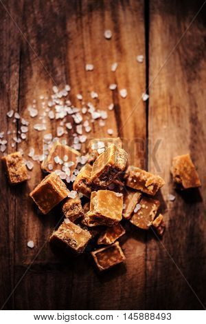 Caramel candies on brown background. Salted caramel pieces and sea salt. Golden Butterscotch toffee caramels. Toffees.