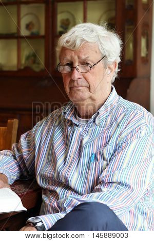 Senior gentleman age 78 reading a book, wearing a hearing aid.