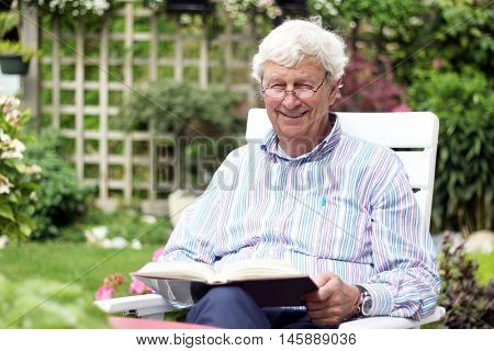 Happy retired gentleman age 78, reading a book in the garden. Visible hearing aid.