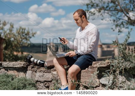 Attractive man working in your home garden. Young man working talking with smart phone in outdoors.