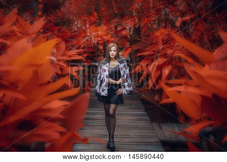 Portrait Of A Beautiful Fashion Girl Wear Traditional Walking On Bridge And Red Tree In Summer