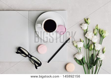 Morning cup of coffee, empty notebook, pencil, glasses, white flowers and cake macaron on light table top view. Beautiful breakfast. Flat lay.