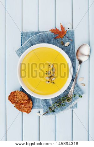 Pumpkin soup decorated seeds and thyme in white bowl on blue vintage table top view. Flat lay styling.