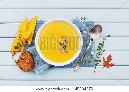 Pumpkin soup decorated seeds and thyme in white bowl on blue table top view. Flat lay styling.
