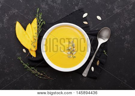 Pumpkin soup decorated seeds and thyme in white bowl on vintage black table top view. Flat lay styling.