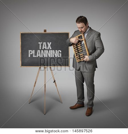 planning text on blackboard with businessman and abacus