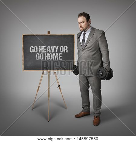 Go heavy or go text on blackboard with businesssman holding weights