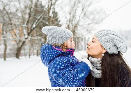 Beautiful young mother with her cute litte daughter on a walk, kissing outside in winter nature