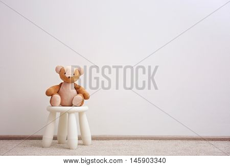 Children stool with toy on white wall background