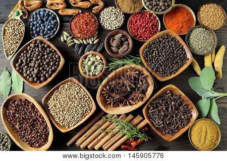 Aromatic spices and herbs in metal and wooden bowls.