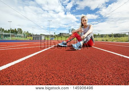 Full length portrait of young woman holding water bottle on running tracks