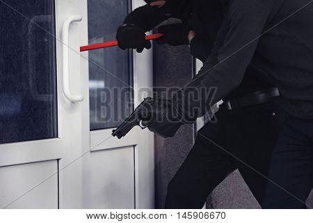 Armed thieves breaking a door