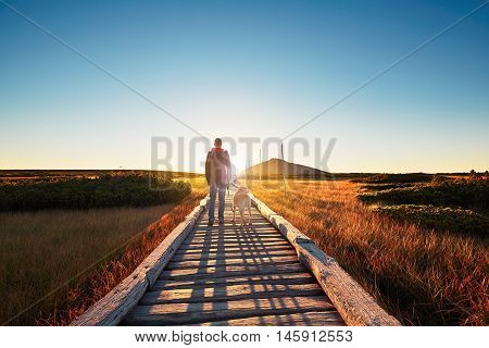 Man with dog on the trip in the mountains. Young tourist and his dog watching the amazing sunrise. Footbridge across the moorland and Snezka - the highest mountain in the Czech Republic.