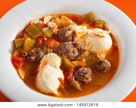 Tunisian soup with meatballs vegetables and poached eggs. Horizontal shot