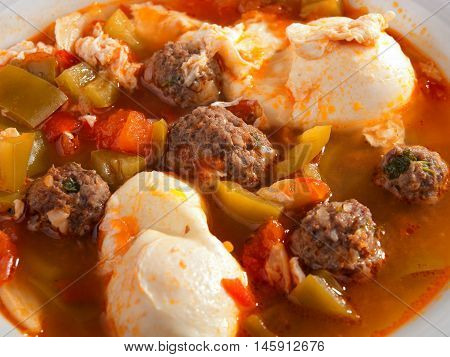 Tunisian soup with meatballs vegetables and poached eggs. Close up horizontal view