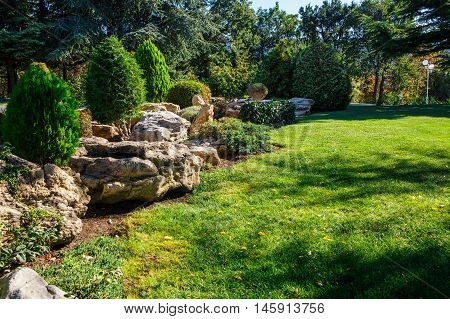 Alpine slide and stones on a green meadow in a landscaped garden in the morning sun