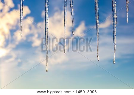Icicles against a blue sky with clouds.