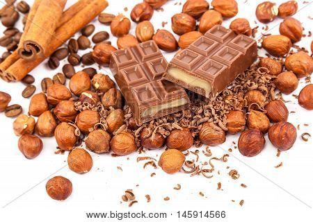 Chocolate nuts and cinnamon sticks isolated on white background.