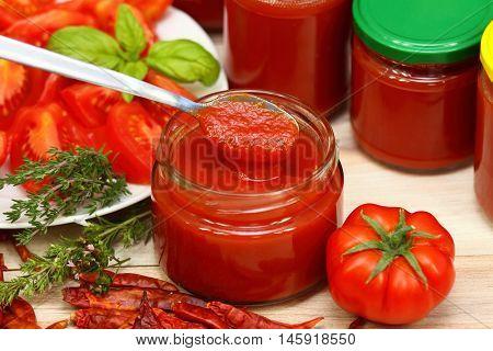 Homemade preservation of ketchup jars of ketchup at background