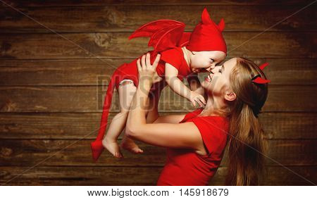 Family fun mother and baby son having fun and celebrate Halloween in devil costume