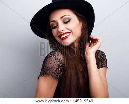 Happy Bright Makeup Lady In Fashion Hat Looking Down With Red Lips In Blue Background