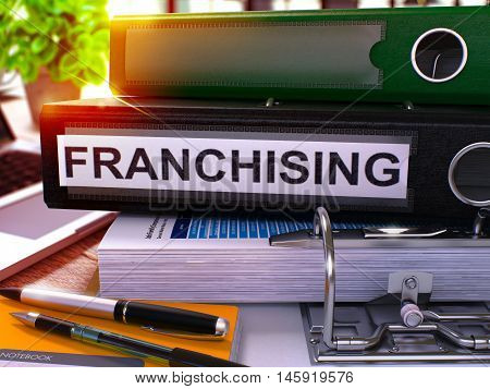 Black Office Folder with Inscription Franchising on Office Desktop with Office Supplies and Modern Laptop. Franchising Business Concept on Blurred Background. Franchising - Toned Image. 3D.