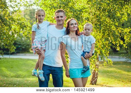 Portrait of young happy ypung family walking in sunny park